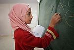 A girl writes on the chalkboard during class in the Zaatari Refugee Camp, located near Mafraq, Jordan. Opened in July, 2012, the camp holds upwards of 50,000 refugees from the civil war inside Syria. International Orthodox Christian Charities and other members of the ACT Alliance are active in the camp providing essential items and services.