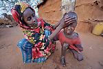 A girl washes her brother's face in the morning in the Dadaab refugee camp in northeastern Kenya. Tens of thousands of newly arrived Somalis who have swelled the population of what was already the world's largest refugee camp.
