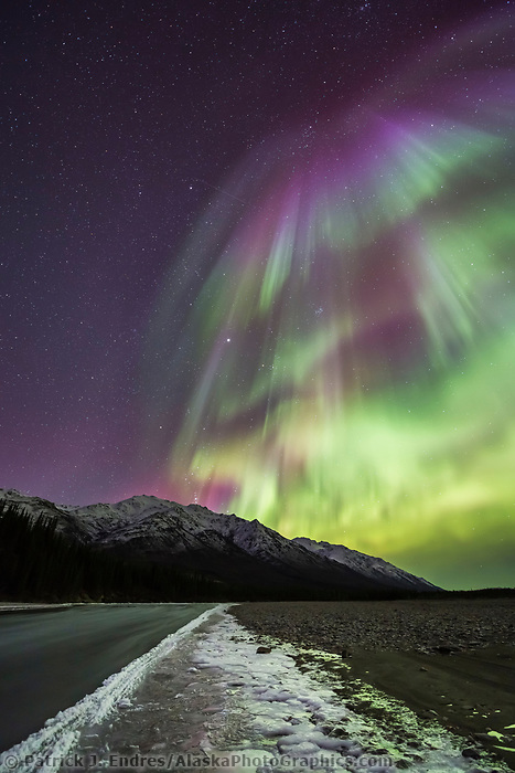 The aurora borealis reflects on the icy surface of a river in Alaska's Brooks range, arctic, Alaska