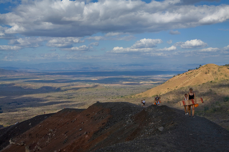 Group of backpackers walk along the craters edge of the active Cerro Negro Volcano, holding wooden sleds and carrying orange protective suits, Nicaragua