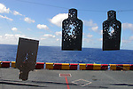 A string of targets riddled by shotgun and automatic and semi-automatic weapons fire hang in various states of destruction after a morning of Marine target practice on the USS Belleau-Wood.