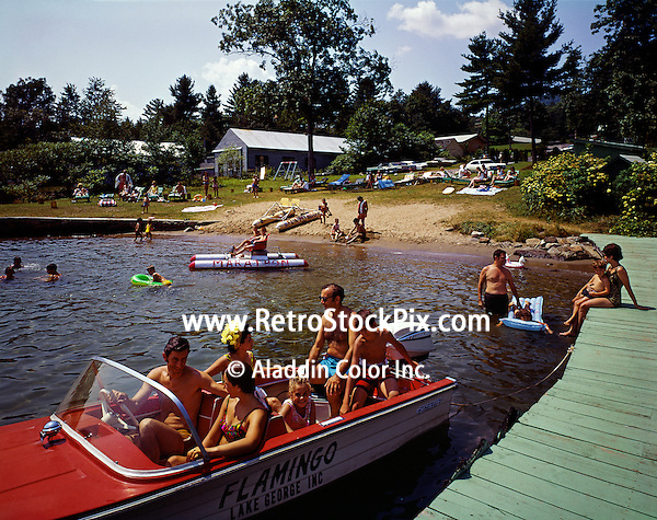 Family riding in wooden boat on Lake George in New York. 1960's retro photograph
