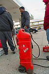 Nov. 3, 2012 - Merrick, New York, U.S. - People wait in line in the cold dusk to fill their gas containers at the Merrick Hess station, one of the Long Island gas stations still open the Saturday after Hurricane Sandy brought severe damage to this south shore area. U.S. Army National Guard members from Syracuse are there to help Nassau County police make sure order is kept. The Freeport Armory in the next town was supposed to have free gas, up to 10 gallons for each car, this day, but people who showed up there were turned away. About 500,000 of the 1.2 million Long Islanders who lost power still don't have it, and the area continues to suffer from severe damage from floods and wind.