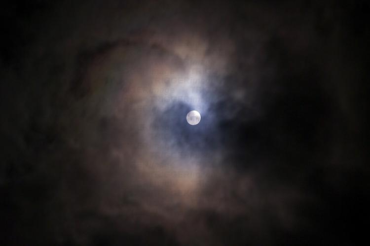 A full moon seen through dense clouds