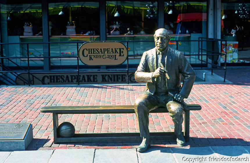 "Boston:  Faneuil Hall Markets--Red Auerback Sculpture.  Red was  personification of basketball's greatest dynasty, the Boston Celtics.  Sculptor Lloyd Lillie, 1985.  Bench encourages  ""sit-by-me"".   Photo '88."