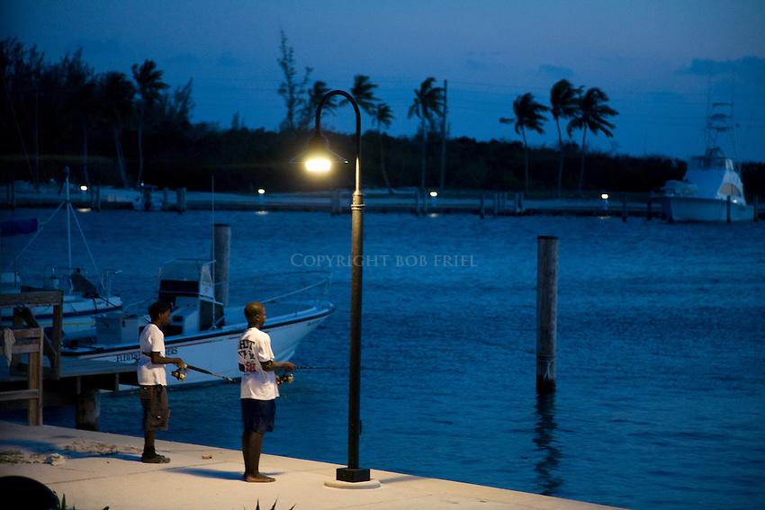 Two young boys fishing at dusk on dock at Cape Eleuthera, Bahamas