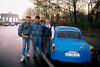 Three East German guys standing next to their Trabant in the Tiergarten, West Berlin, on the morning of November 10, 1989, hours after the opening of the Berlin Wall. They have just crossed over the border at Checkpoint Charlie to the West for the first time in their lives. In the background is the Wall and the Brandenburg Gate..