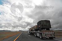 Americana Series: Road Trip<br /> <br /> Military Truck transport convoy in desolate area of Northern New Mexico with storm clouds brewing.