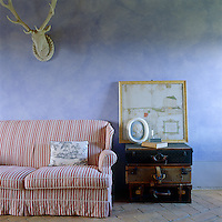An antique map in the living room is propped on a side table inventively constructed from antique suitcases