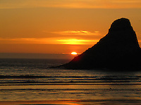 As it slips into the Pacific, the sun casts a warm golden glow at the beach below the Haceta Head Lighthouse north of Florence, Oregon.