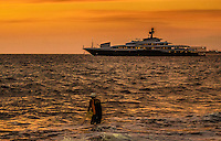 Fine Art Print photograph. Sunset scene of a large ocean yacht anchored in Banderas Bay Puerto Vallarta, Mexico. The lighting was beautiful, and the net fisherman in the foreground of this scene balanced this sunset photograph of the warm lighting that was producing a textured glow upon the ocean waves.