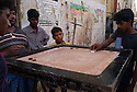 Boys playing a board game on the streets of the Santhome flat complex. Santhome Beach and adjoining Marina Beach in Chennai, India were hit hard by the 2004 Tsunami. Fishermen and their families were the main victims living in their lightweight huts on the long and flat beaches of the area. All structures within 300 metres of the sea have now been banned and any left standing after the Tsunami were demolished. The fishermen and their families have now been relocated to government blocks of flats which has become a Santhome slum for fishermen and their families.