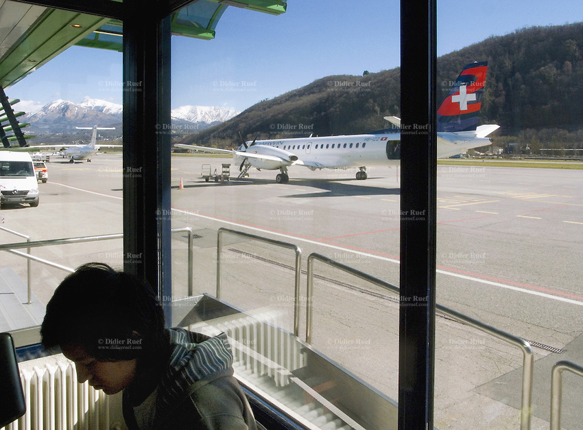 Switzerland. Canton Ticino. Lugano Airport is located in Agno, distant 10 km from downtown Lugano. A Darwin airplane is on the strip. A passenger is waiting for the departure of his flight. Swiss flag. 260309 © 2009 Didier Ruef
