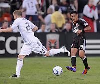 D.C. United midfielder Andy Najar (14) goes against Vancouver Whitecaps FC defender Jordan Harvey (26). D.C. United defeated The Vancouver Whitecaps FC 4-0 at RFK Stadium, Saturday August 13 , 2011.