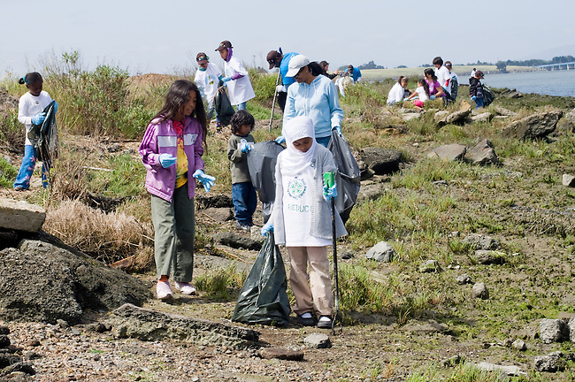 Oakland CA Preteen girls and parents involved in beach clean up on shores of San Francisco Bay on.Earth Day
