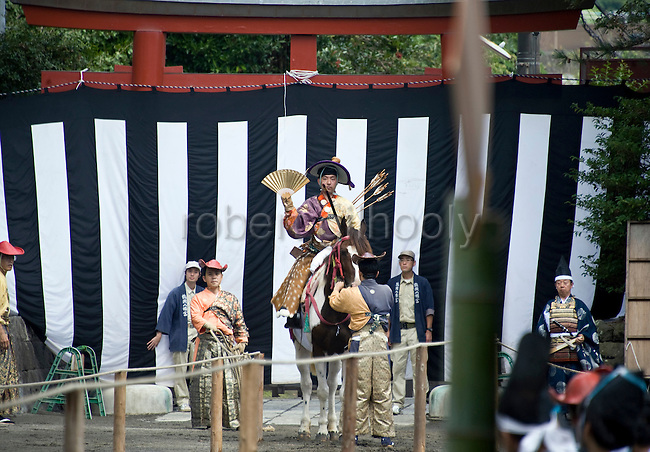 A horseback archer prepares to throw a golden fan in the air to mark the first run in the yabusame horseback archery ritual during the the annual Reitaisai Grand Festival at Tsurugaoka Hachimangu Shrine in Kamakura, Japan on  14 Sept. 2012.  Sept 14 marks the first day of the 3-day Reitaisai festival, which starts early in the morning when shrine priests and officials perform a purification ritual in the ocean during a rite known as hamaorisai and limaxes with a display of yabusame horseback archery. Photographer: Robert Gilhooly
