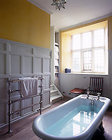 A vintage towel rail complements the wood panelled walls and the free standing bath  in this bathroom