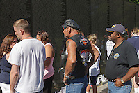 Visitors reflect while viewing names on the Vietnam Veterans Memorial in Washington, DC.