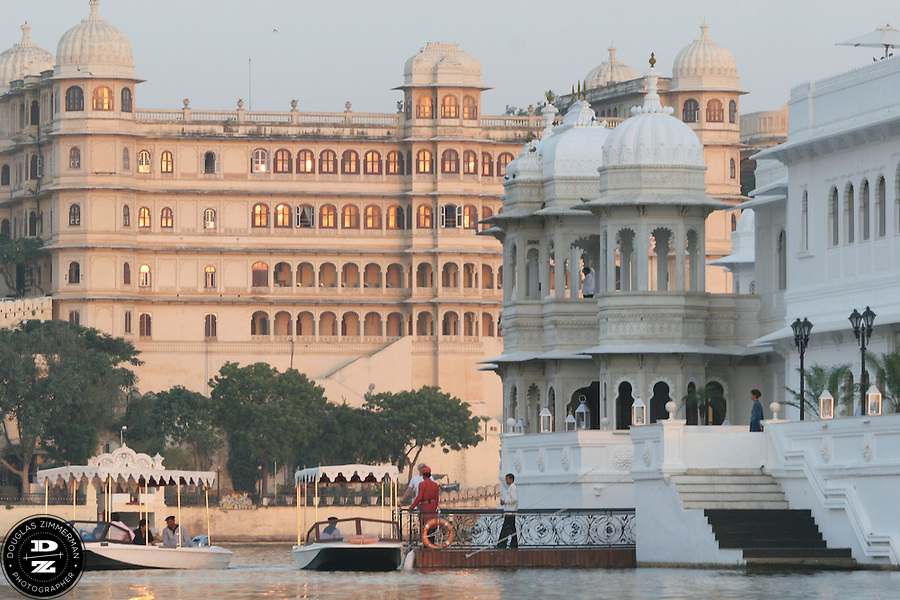 "View of the Lake Palace Hotel, which sits on Jagniwas Island in the center of Pichola Lake, with the Fateh Prakash Palace Hotel in the background in Udaipur, Rajasthan, India.  Udaipur is located in a valley surrounded by the Aravalli hills, and at its center is the Pichola Lake.  The scenic city has been described as ""the most romantic spot on the continent of India"" (by Colonel James Tod).  Photograph by Douglas ZImmerman"