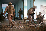 Marines from Company L, 3rd Battalion, 6th Marine Regiment take cover from Taliban fire inside an abandoned school near Marjah, Afghanistan as they wait for a medevac helicopter to extract a wounded Lance Cpl. Matthew W. McElhinney. The sporadic shooting continued for 20 minutes before the Taliban broke off their attack. March 10, 2010. DREW BROWN/STARS AND STRIPES
