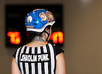 Outside pack referee Shaolin Punk of OCRG stands at the ready in front of the out of focus / blurry scoreboard.  Her custom painted blue and white Derby Skulz helmet sparkles.