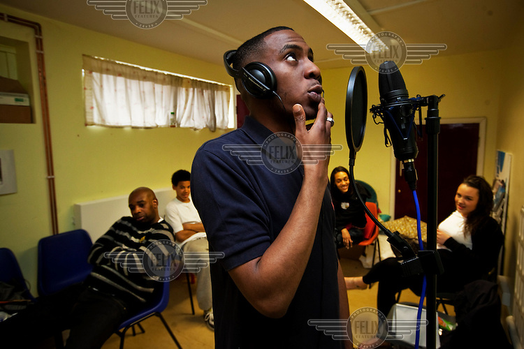 A young man rapping in a recording studio in the London Borough of Hackney.