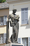 A World War II memorial with a statue of a woman holding a sword and a palm leaf in Tremezzo, a town on Lake Como, Italy.