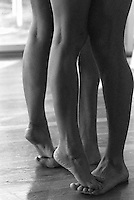 Detail of legs and feet of a couple; woman stands on man's toes.