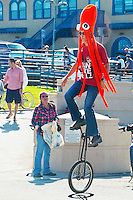 A man wearing an octopus cap rides a unicycle along the Santa Monica Boardwalk on Sunday, July 15, 2012..