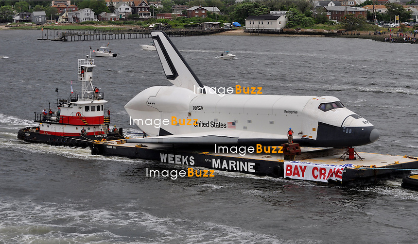 The space shuttle Enterprise, atop a barge,  passes the Statue of Liberty in New York on its way to the Intrepid Sea, Air and Space Museum where it will be permanently displayed, Wednesday, June 6, 2012.