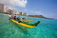 Kids enjoying a Hawaiian outrigger canoe ride off the shores of Waikiki