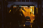 Ferry boat with silhouetted worker directing traffic coming onto ferry at sunset Seattle Washington State USA