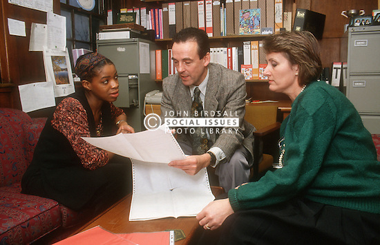 Three teachers meeting in head teacher's office discussing computer printout,
