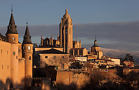 The towers of the Alcazar, 12-16th centuries, (left) and Segovia Cathedral, (Catedral de Segovia, Catedral de Santa Maria), 1525-77, by Juan Gil de Hontanon (1480-1526), and continued by his son Rodrigo Gil de Hontanon (1500-1577) (right), Segovia, Castile and Leon, Spain, with the  mountainous winter landscape in the background. Picture by Manuel Cohen
