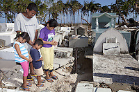 Philippines. Province Eastern Samar. Hernani.  Graveyard. The Calvadores family with the mother Juvac (right), the father Nelson ( center) and their two children Marie Grace and Elmerson. They pray on the grave of their deceased son and brother Winston, 5 months old who passed away during Typhoon Haiyan. 95 % of the town was destroyed by typhoon Haiyan's winds and storm surge. Typhoon Haiyan, known as Typhoon Yolanda in the Philippines, was an exceptionally powerful tropical cyclone that devastated the Philippines. Haiyan is also the strongest storm recorded at landfall in terms of wind speed. Typhoon Haiyan's casualties and destructions occured during a powerful storm surge, an offshore rise of water associated with a low pressure weather system. Storm surges are caused primarily by high winds pushing on the ocean's surface. The wind causes the water to pile up higher than the ordinary sea level. 25.11.13 © 2013 Didier Ruef