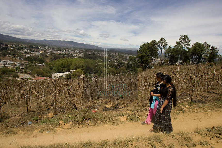 Maria (right), 16, and her friend, Alma de Los Angeles Sambrano Montufa, 15, walk in Alma's neighborhood in Chimaltenango, Guatemala on Thursday, March 8, 2007. Maria works at Legumex, a vegetable and fruit company that exports to the United States. She injured her wrist on the job and couldn't work today. Alma recently quit the company after a year and a half.