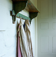 A pair of coats hangs from a old painted rack in a hallway