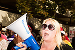 July 13, 2015. Winston Salem, North Carolina.<br />  Kim Porter, a community organizer and an arrestee of the Moral Monday protests, chants as she marches to support the NC NAACP's voting rights case against Gov. Pat McCrory.<br />  To rally support for the North Carolina NAACP's case against Gov. Pat McCrory (NC NAACP v. McCrory), a march was held in downtown Winston Salem on the opening day of the case in federal court. Thousands gathered to walk the streets of downtown and listen to speeches proclaiming the importance of defeating new requirements for voter registration,<br />  The NC NAACP contests that HB 589 (Voter ID requirements) violate Section 2 of the Voting Rights Act (42 U.S.C. 1973) and the Fourteenth and Fifteenth Amendments of the Constitution.