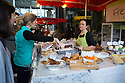 London, UK. 25.10.2014. A woman serving a customer on a pasties and cake stall at Borough Market, Southwark. Photograph © Jane Hobson.