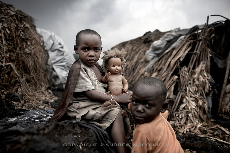 Displaced children sit outside their makeshift homes in the Mugunga 1 IDP site, home to some 10,000 people, in Goma, North Kivu, DRC.