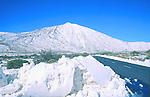 Road running through the Cañadas national park. Snow capped Mount Teide, Tenerife, Canary Islands.