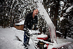 Jim Wilcox blows snow off his driveway in Homewood, Calif. on the shores of Lake Tahoe, February 28, 2012..