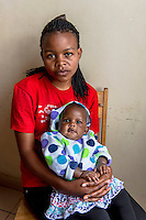 "Africa, DRC, Democratic Republic of the Congo, Goma, Lake Kivu,  Global Fund for Women. Stop violence in schools campaign by the PAIF organization project. Kisonga Matondo (17 yrs) is an orphan, her mother died at 3 months, her father when she was 8. At 13 she was raped by her 52 yr old teacher while in secondary school. She was afraid to tell anyone but she became pregnant, her baby is now 4 yrs old. The school did nothing. One day she was picked up by a man in his car, working on the boat transport system, who gave her a ride in the rain. He raped her. The baby she is holding is her second from a rape. When she became pregnant her took her in but beat her everyday, and she discovered she was his sixth wife and this was his 8th child. ""I suffered suffered suffered, but  had no one to take care of me until I met with PAIF."" PAIF will help to sue her husband but if they lose he will kill her. There is no justice in this country."