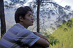 Asia, Nepal, Kathmandu. A young teenager contemplates life in nature.
