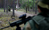 Soldiers encounter a jogger in a forest during a reconnaissance mission. Norwegian Home Guard soldiers during exercise Djerv..The Home Guard has traditionally been designated to secure important  domestic installations in case of war or crisis. With the cold war long gone, a war in Afghanistan and budget cuts, there is a debate over the Home Guard's role in the future.