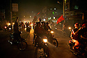 Hundreds of vehicles honk in the dark streets lit only by their lights. Myanmar. 2012