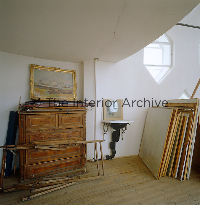 An antique chest of drawers and a stack of paintings in a corner of the atelier