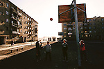 Impromptu basketball game outside the apartment building in Sector 21 where Oyuntsetseg and Regzen Batsuuri live with their two children in Ulaanbaatar, Mongolia. From coverage of revisit to Material World Project family in Mongolia, 2001.