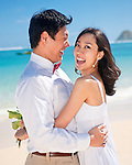 Asian couple embrace during their honeymoon on Lanikai beach, Kailua, Hawaii