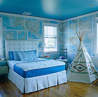 National Geographic Society maps cover the walls of this boy's bedroom, furnished with a generous bed and a hand-painted teepee
